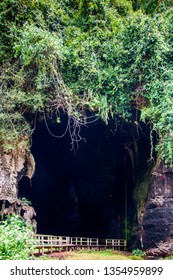 Kota Kinabatangan, Sabah, Malaysia - Juli 27 2014: The Gomantong Caves, a traditional place for harvesting birdnests, seen from outside. A walkway is leading into the cave.