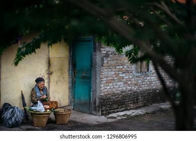 Kotagede, Jogjakarta / Indonesia - July 26, 2016 : an old woman selling traditonal food at corner of Kotagede alley.