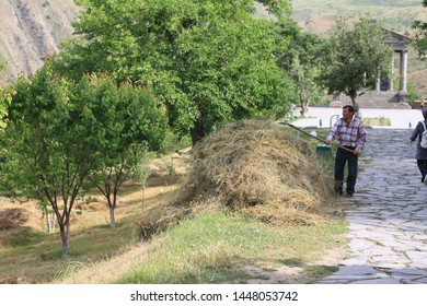Kotayk, Armenia- In front of the ancient Roman temple in Garni in Armenia, a peasant is cleaning the garden.June 21, 2010.