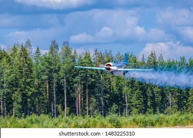 KOTKA, FINLAND - Aug 10, 2019: Two-seat single-engined piston-powered Yakovlev Yak-52 primary aerobatic trainer aircraft OH-YAC performs aerobatics at Karhula aviation museum airshow.