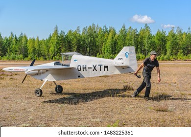 KOTKA, FINLAND - Aug 10, 2019: Pilot tug their self-made single-engined piston-powered airplane PIK-21 Super-Sytky OH-XTM to the parking on the Karhula aviation museum airshow.