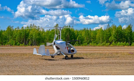 KOTKA, FINLAND - Aug 10, 2019: Italian sport autogyro Magni M-24 Orion (OH-G016) with two side-by-side seats in an enclosed cabin taxis for takeoff at Kymi (EFKY) airfield.