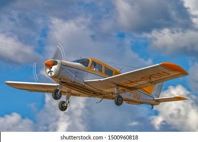 KOTKA, FINLAND - Aug 10, 2019: Four-seat light all-metal single-engined piston-powered airplane Piper PA-28-140 Cherokee Cruiser OH-PDU flying in a blue sky against a background of white clouds.