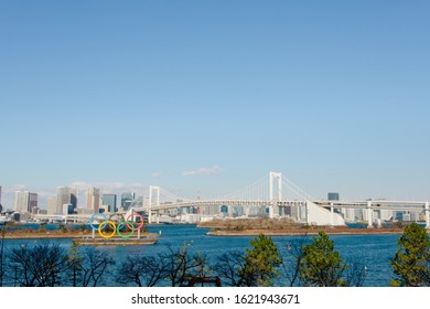 Koto Minato, Tokyo / Japan - January 21 2020: Five gigantic Olympic rings, just installed, in front of the famous Rainbow Bridge at Tokyo Bay, Odaiba Marine Park, a venue of Tokyo Summer Olympics 2020