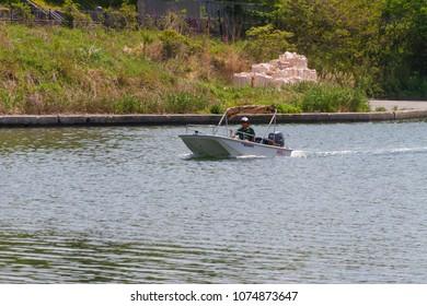 Koto-ku, Tokyo, Japan. April 20, 2018. A man rides in a small motorboat on the Kyunaka River in Eastern Tokyo.