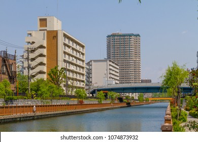 Koto-ku, Tokyo, Japan. April 20, 2018. Two 20th century public housing apartment buildings and a tall modern high-rise  overlook the Onagi River in eastern Tokyo.