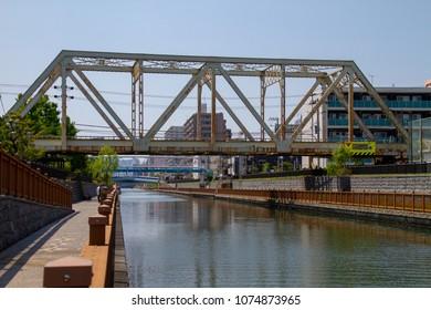 Koto-ku, Tokyo, Japan. April 20, 2018. An old, rusty, steel industrial railway bridge over the Onagi River in eastern Tokyo.