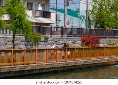 Koto-ku, Tokyo, Japan. April 20, 2018. An elderly couple walk along the pedestrian pathway next to the Onagi River in eastern Tokyo.