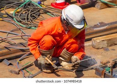 Koto-ku, Tokyo, Japan. April 20, 2018. A man does welding on a barge.