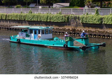 Koto-ku, Tokyo, Japan. April 20, 2018. River cleaning boat and workers on the Onagi River in eastern Tokyo.