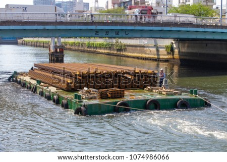 Koto-ku, Tokyo, Japan. April 20, 2018. A small tugboat tows a barge load of steel on the Onagi River in eastern Tokyo.