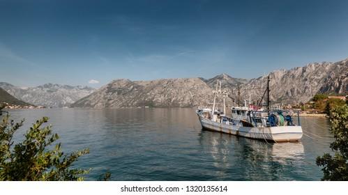 Kotor bay coastline with fishing vessel  Montenegro