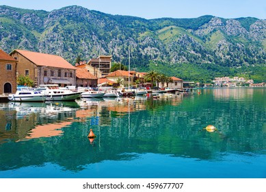Kotor coastal town, old Mediterranean port, in secluded part of Bay of Kotor (Boka Kotorska) with yachts and fishing boats, Montenegro. Mirror Adriatic Sea surface and idyllic seascape.