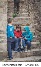 Kotor, Montenegro - April 2018 : Montenegrin children sitting on stairs and playing games on a small electronic device, Kotor Old Town