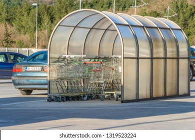 Kotor, Montenegro, February 15, 2019: Parking at the KIPS hypermarket. Hypermarket trolleys are standing near the entrance under a canopy
