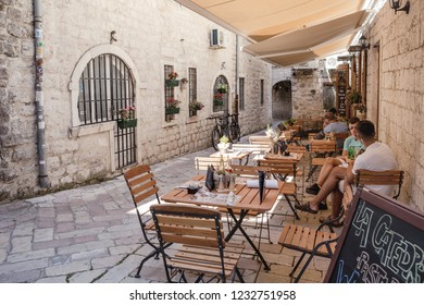 KOTOR, MONTENEGRO - JULY 18, 2018: People eating in cafe on the narrow street in the old town of Kotor, Montenegro