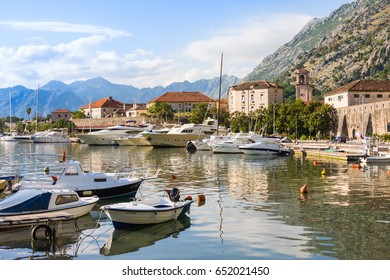 KOTOR, MONTENEGRO - JUNE 24, 2015: The boats in sea at sunset with mountains and old city
