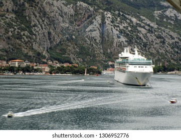 Kotor, Montenegro, June 28, 2018.  Cruise liner manoeuvring in the Bay of Kotor just off Kotor walled old town harbour.  Pilots boats in view. Kotor, Montenegro, June 28, 2018.