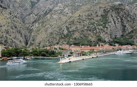 Kotor, Montenegro, June 28, 2018.  Kotor dock and walled old town at the base of mountain.  Shot from departing cruise ship.  Kotor, Montenegro, June 28, 2018.