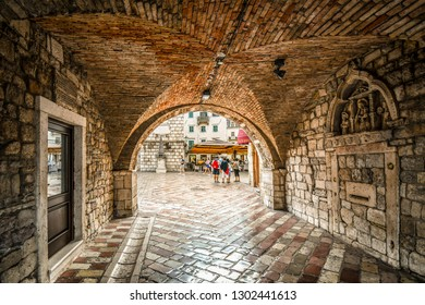 Kotor, Montenegro - September 14 2018: The Square of the Arms opens out  in front as tourists enter the gated, walled medieval fortress town of Kotor, Montenegro through it's tunnel entrance.