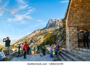 Kotor, Montenegro - September 15 2018: A stray cat watches tourists rest at a stop along the steep path of the Castle of San Giovanni ruins, or Kotor Castle, in Kotor, Montenegro, the City of Cats.
