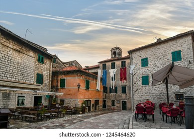 Kotor, Montenegro - September 16 2018: An oversized display of laundry hangs over a small village square with cafes and outdoor dining in the medieval city of Kotor, Montenegro.
