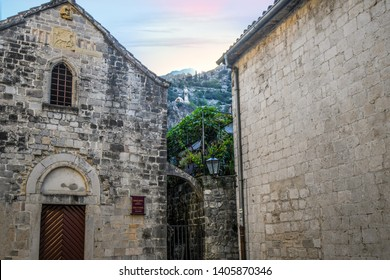 Kotor, Montenegro - September 17 2018: The church tower of the Castle Of San Giovanni, or Kotor Castle, is visible between two medieval buildings in the city of Kotor, Montenegro.