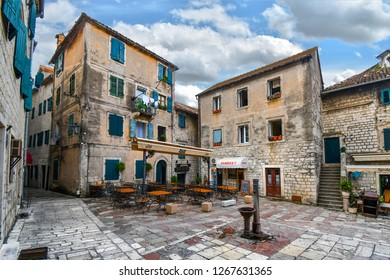 Kotor, Montenegro - September 18 2018: A small square in Old Town Kotor, Montenegro, with a water pump in the center surrounded by a cafe, market and apartments with colorful window shutters.