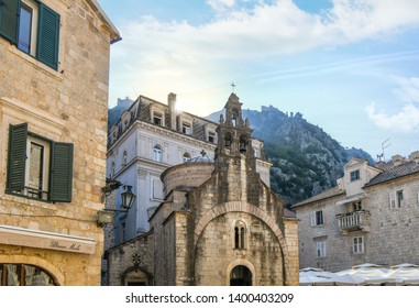 Kotor, Montenegro - September 19 2018: Sunlight shines behind the mountains above the tower and bells of St. Luke's Church in Luke's Square, in Kotor, Montenegro.