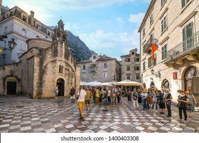 Kotor, Montenegro - September 19 2018: Tourists gather on St Luke's square in front of the old church with it's three bell towers in Kotor, Montenegro.