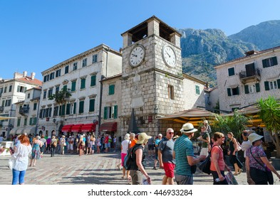 KOTOR, MONTENEGRO - SEPTEMBER 22, 2015: Unidentified tourists are walking near ancient Clock tower on Plaza of Oruzja in Old Town of Kotor, Montenegro