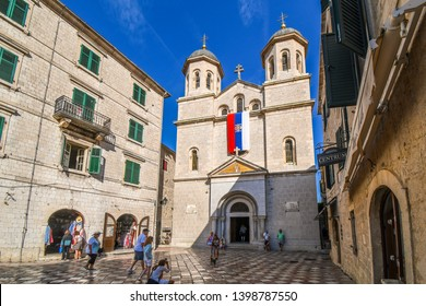 Kotor, Montenegro - September 22 2018: Tourists and a cat sightsee in front of the Nicholas Church, a Serbian Orthodox Church in the Old Town center of Kotor, Montenegro.