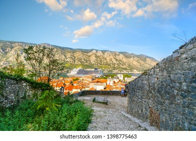 Kotor, Montenegro - September 23 2018: View from the hillside Kotor Castle of a large cruise ship sits in the harbor next to the medieval walled old town at the cruise port of Kotor Montenegro.