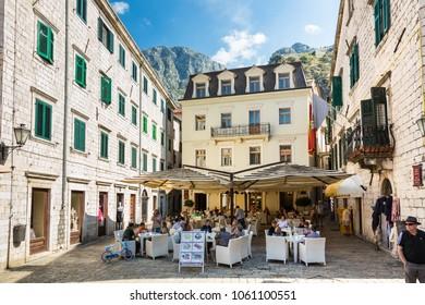 KOTOR, MONTENEGRO - september 25, 2016: People hide in a shade under restaurant umbrellas in Stari Grad on a sunny day in Kotor, Montenegro