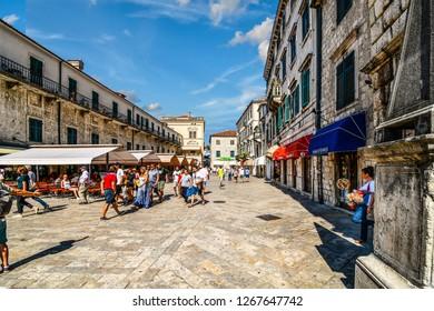 Kotor, Montenegro - A young woman selling souvenirs takes a cigarette break in the shade in the Piazza of the Arms in the ancient city of Kotor, Montenegro as tourists walk by the cafes and shops