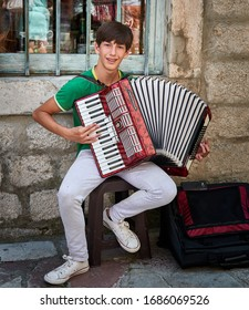 KOTOR, MONTENEGRO-July 2, 2019: Philip, a local boy playing accordion on the streets of Kotor.
