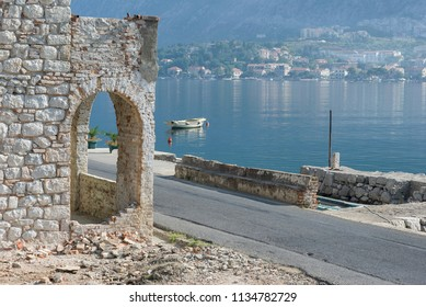 Kotor in the morning/Blue water bay and hazy morning beyond the white stone of the quay buildings.
