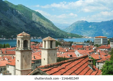 Kotor old town with the towers of a church seen from above, the mountains of the bay of Kotor (Kotorska Boka) can be seen behind. Kotor is a coastal town in Montenegro.