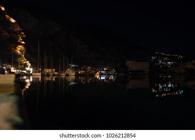 Kotor Promenade and Port with Reflection of City and Boats in the Adriatic Sea at Night, Montenegro