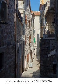 Kotor/Montenegro - August 13, 2018: Narrow street between houses in the old town of Kotor, Montenegro, air conditioners on buildings, window shutters on windows