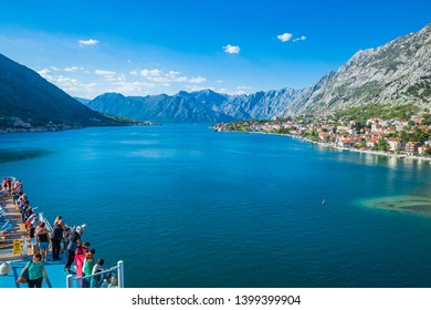 KOTOR,MONTENEGRO-APRIL 19,2019:  Tourists on the boat terrace See historic town of Kotor and beautiful mountains
