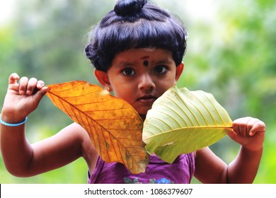 Kottayam, Kerala/ India- March 04, 2015: A happy, smiling, cute little girl child playing with leaves