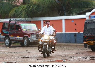 Kottayam, Kerala/India- June 30, 2018: Handsome groom/young man and brother in traditional dhoti and shirt riding on a Royanl Enfield. Monsoon morning scene from a village.