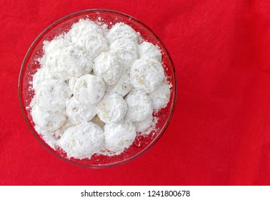 """""""Kourabiedes"""" traditional Greek Christmas cookies covered with powdered sugar, on red background"""