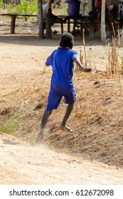 KOUTAMMAKOU, TOGO - JAN 13, 2017: Unidentified Togolese little boy in blue suit runs in the village. Togo children suffer of poverty due to the bad economy.