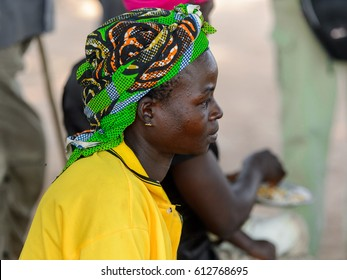 KOUTAMMAKOU, TOGO - JAN 13, 2017: Unidentified Togolese woman in yellow shirt and headscarf sits in the village. Togo people suffer of poverty due to the bad economy.
