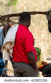 KOUTAMMAKOU, TOGO - JAN 13, 2017: Unidentified Togolese man in red shirt from behind in the village. Togo people suffer of poverty due to the bad economy.