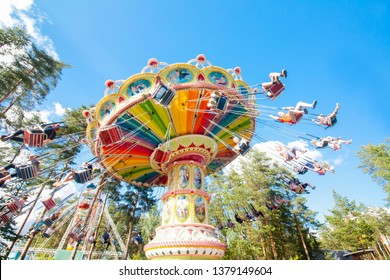 Kouvola, Finland - 13 July 2017: Colorful chain swing carousel in motion at amusement park Tykkimaki on blue sky background.