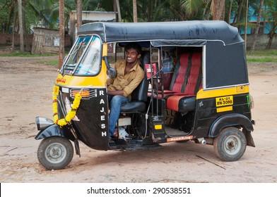 KOVALAM, INDIA - DEC 28, 2014: Indian auto rickshaw with taxi driver man in fishing village. Kovalam. Kerala. India