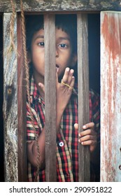 KOVALAM, INDIA, DEC 28, 2014: Unidentified Indian boy looks through a window at home in small fishing village